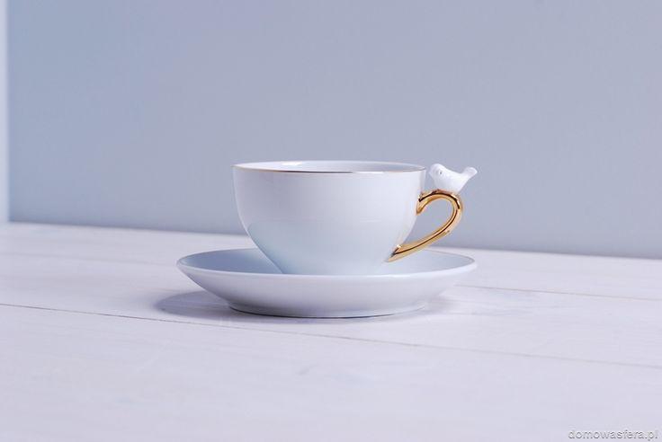 Komplet 2 filiżanek z talerzykami. Filiżanki wykonane z cienkiej białej porcelany, przyozdobione złotymi akcentami oraz małym ptaszkiem.