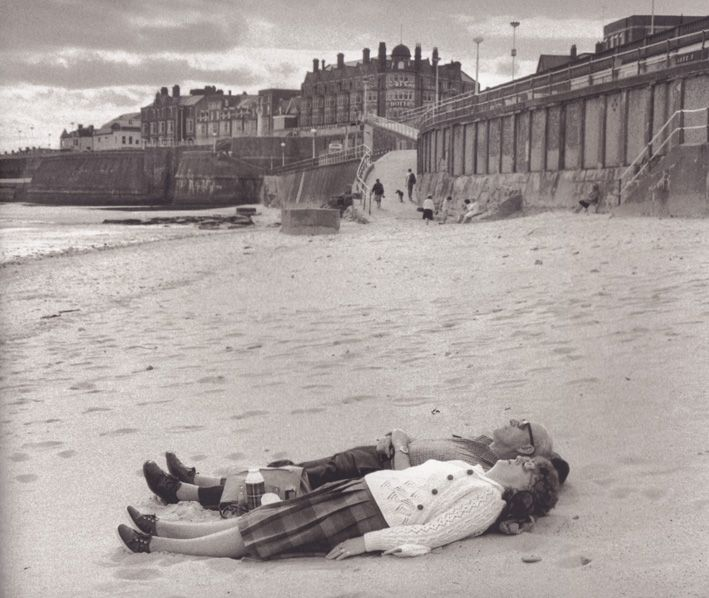 A couple lying on Whitley Bay Beach in United Kingdom.