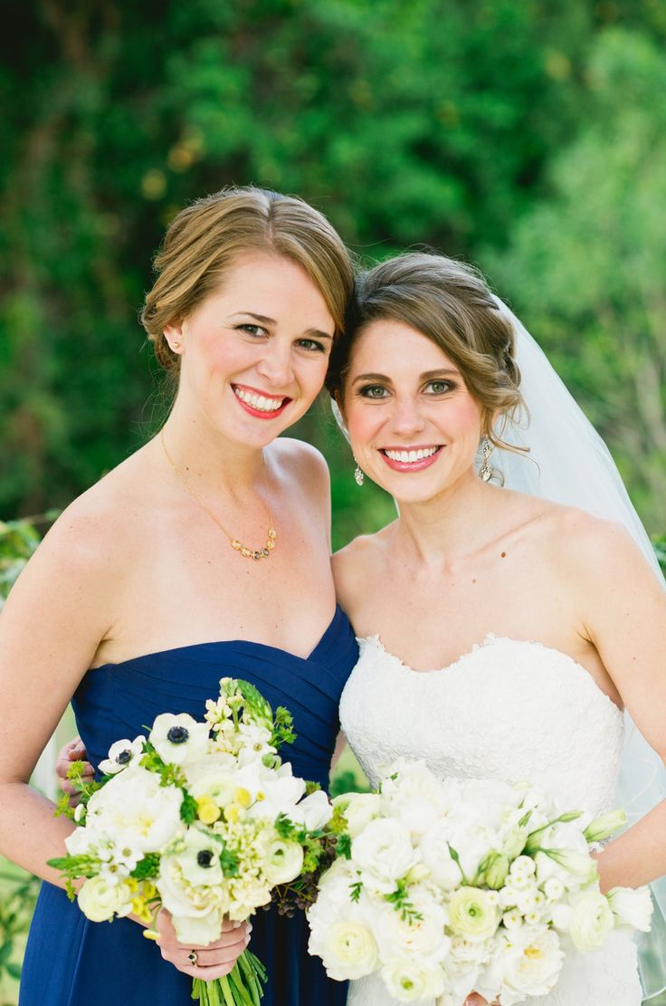 the bride and her bridesmaid share a sweet moment. bridesmaid bouquets of white peony, pale yellow stock, white tulips, pale yellow ranunculus, bupleurum, yellow stock, button chamomile, anemones, Amelia roses, white star of Bethlehem and privet berry wrapped in cream satin ribbon