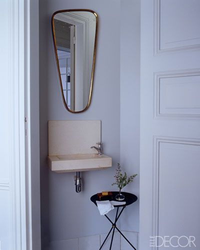 A circa-1950 brass mirror hangs in the powder room of the Paris pied-à-terre shared.