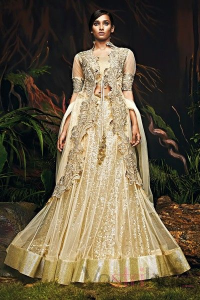 The lehenga and dupatta are in cream color, and the choli is in gold. Heavy Indo-western net lehenga embellished with sequins and decorated with cut work along the border. Comes with exquisite diamond worked dupatta and pure gota blouse.