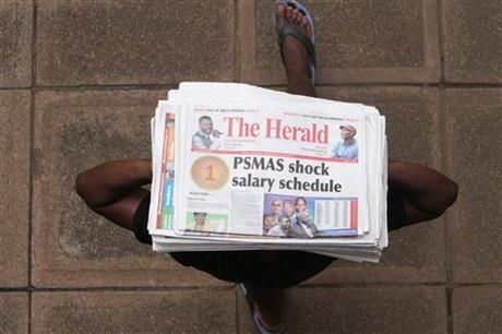 A newspaper vendor carries newspapers for sale with a headline detailing a shocking salary schedule for top executives at a Medical aid society in Harare, Tuesday, February, 4, 2014. (AP Photo/Tsvangirayi Mukwazhi) ▼4Feb2014AP|Zimbabwe takes aim at corruption http://bigstory.ap.org/article/zimbabwe-takes-aim-corruption