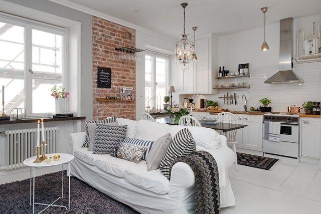 papier peint brique rouge et un canapé blanc dans le salon ouvert sur la cuisine