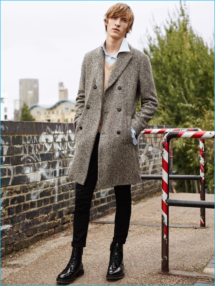 Tim Dibble dons a double-breasted herringbone coat with a cashmere sweater, striped shirt, black jeans, and boots by Zara Man.
