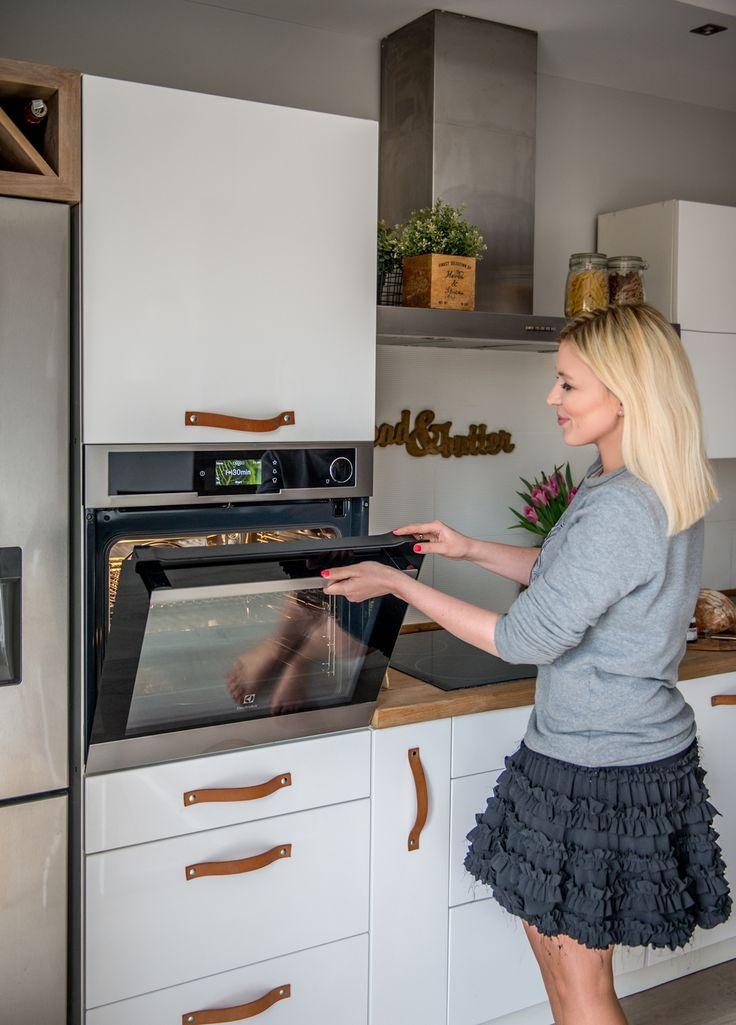 Białe szafki z drewnianym blatem i nowoczesny piekarnik w kuchni