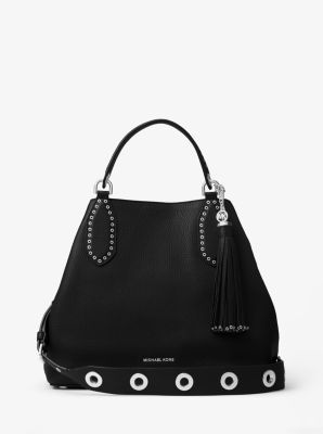 Pensé pour toutes les circonstances, le sac à main Brooklyn adopte un look bohème cette saison, avec sa silhouette ample et sa grande bandoulière ornée d'œillets brillants. Ce modèle épuré en cuir doté d'un pompon surdimensionné est agréable au toucher, et le logo de la marque offre une note raffinée et glamour.