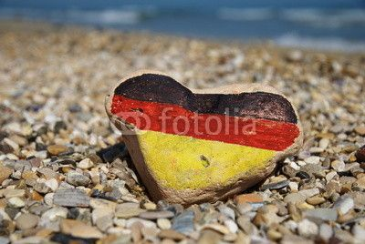 Flag of Germany on a stone heart over many pebbles of the beach