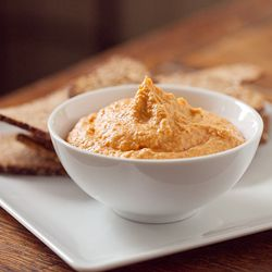 Roasted Red Bell Pepper Hummus/ 1 (15 ounce) can garbanzo beans, drained   1 tbsp tahini paste   1 head garlic, cloves separated and peeled, and coarsely chopped   1/4 c olive oil   1 red bell pepper   4 tbsp Greek style yogurt  Place the beans, bell pepper, tahini, and yogurt into the bowl of a food processor. Spoon out the garlic and some of the oil in with the other ingredients. Reserve the remainder of the oil for other purposes. Process until smooth and season with salt