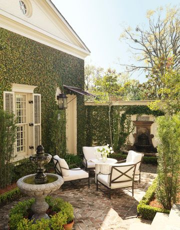 "love the covered walls & the sense of intimacy: Outdoor Courtyard The patio was inspired by the intimate, romantic courtyards in the French Quarter. ""It's totally hidden from street view, so it creates a sense of privacy and mystery,"" says designer Ty Larkins. The Carmel armchairs are by Restoration Hardware."