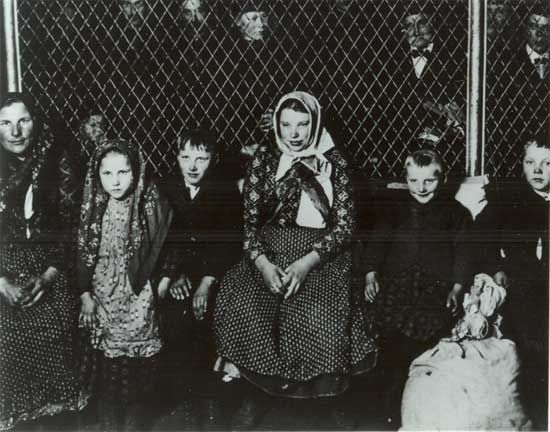 Approved for entry, these immigrants wait in the Ellis Island Railroad Ticket Office.