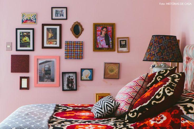Composição de quadros e pequenos objetos na parede desse quarto étnico e colorido.