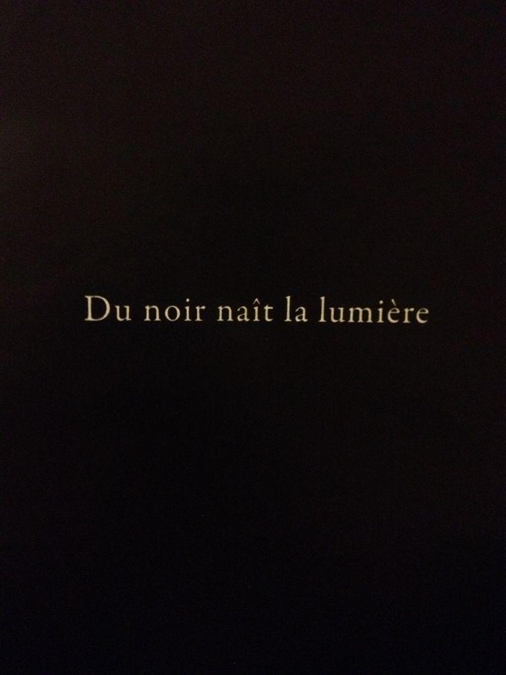 "Coco Chanel. Translates to ""Through black...light revealed."""