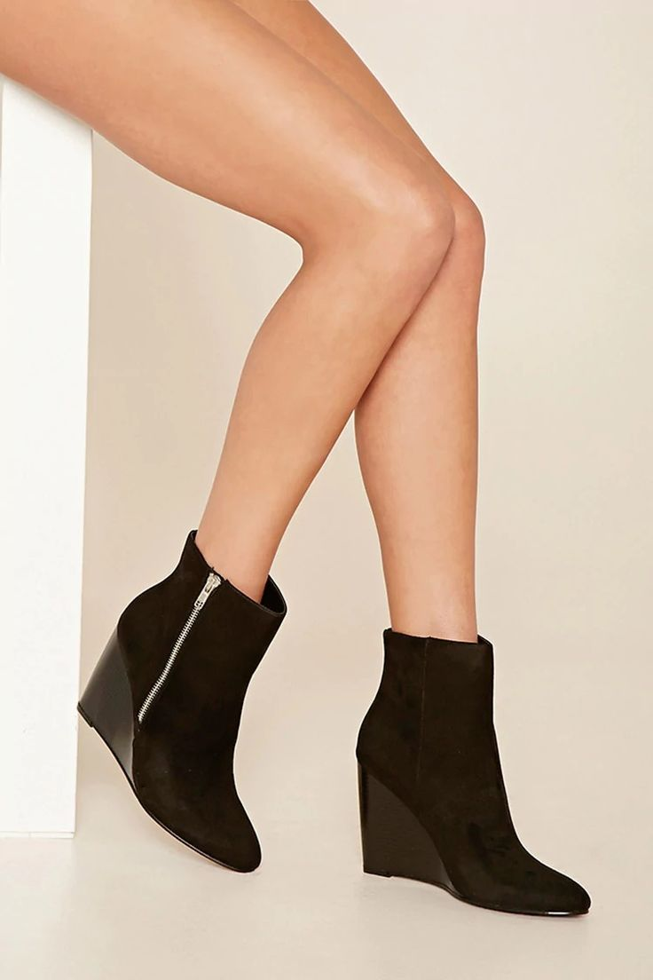 A pair of faux suede ankle boots featuring  a wedge heel, an exposed side zipper, a slightly pointed toe.