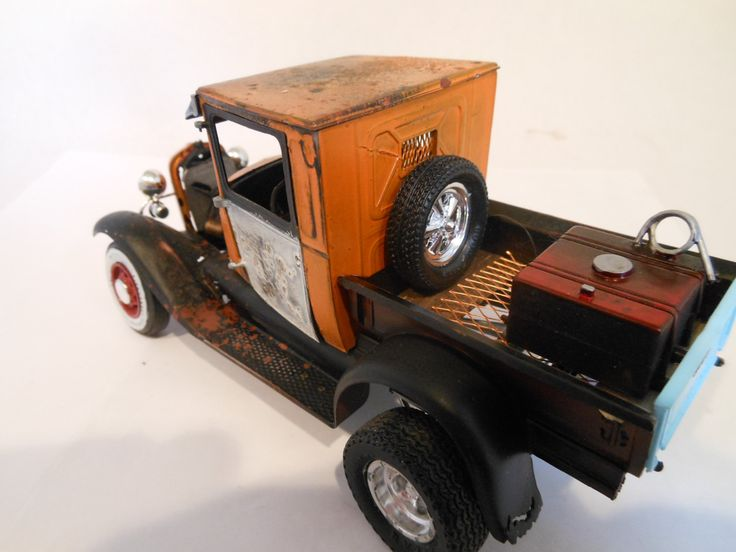 Here is a 1929 Ford Truck in orange and blue. Its has a rat rod look. The orange paint is pitted and blotchy. The cargo box is gutted but redone with metal mess. There is a spare tire and large gas tank in the cargo box. The tires are mixed up with red wire rims on the front with old school whitewall tires and mag wheels on the rear. A nice ride with an old school look. It measures six inches long and 4 inches high.