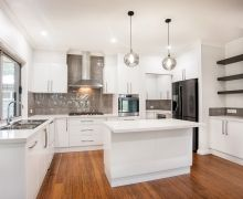 Classically elegant with white gloss cabinets, white stone benchtops, bamboo flooring and gloss tile splashback. Walks through to scullery and pantry.