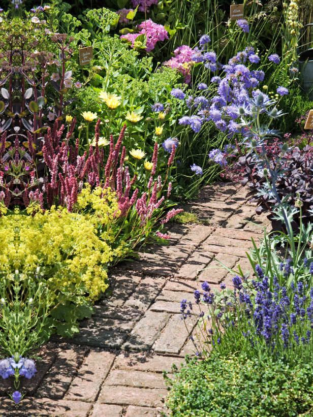 english country style garden features colorful mix and a brick path - English Country Garden Design
