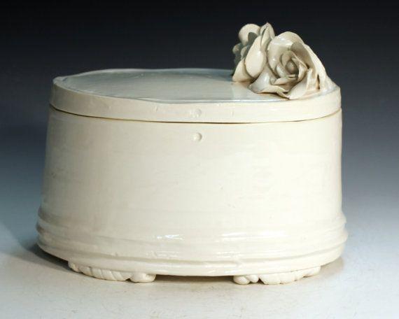 Een keramieke urn met een bloem erop   Vind meer inspiratie over de romantische uitvaart op http://www.rememberme.nl/romantische-uitvaart/