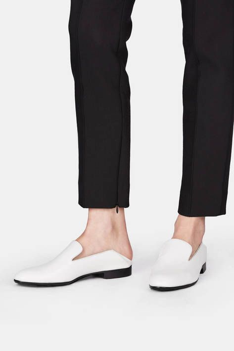 "This slip-on, in smooth white calfskin with a black leather sole, is inspired by the traditional Moroccan slipper known as the babouche. The ""step-down"" touch of a collapsible back makes for a style that is at once boyish, relaxed, and exotic."