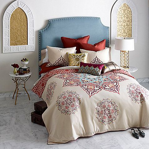 The vibrant design of these Chanda Duvet sets feature a vivid oversized medallion encircled by intricate medallion accents over khaki. Metallic bronze embroidery across the duvet and two heavily embroidered matching shams complete the luxe look.