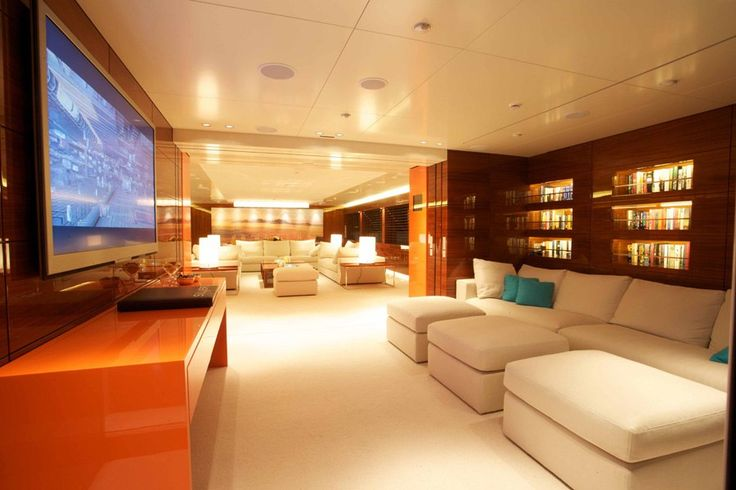 glossy wood finishes and luxurious white leather sofas. Outdoor features include dining spaces, a Jacuzzi, a large sundeck