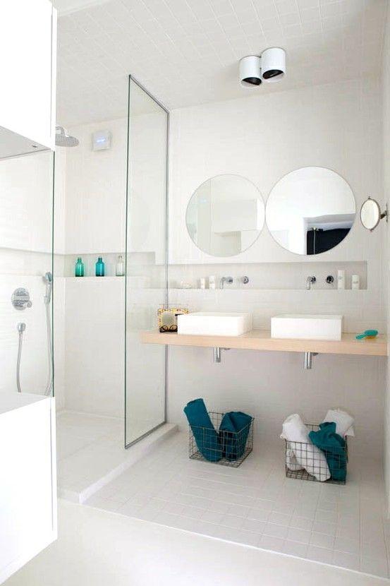 reforma baño pequeño, lavabos de diseño sobre encimera de madera, espejos circulares, paredes y suelo de azulejo pequeño formato, zona de ducha con separación de vidrio. presupuestON.com