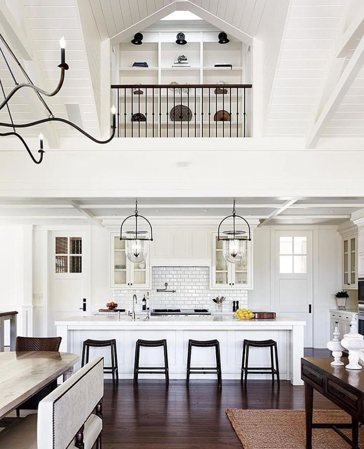 White kitchen with open view to upstairs book shelves