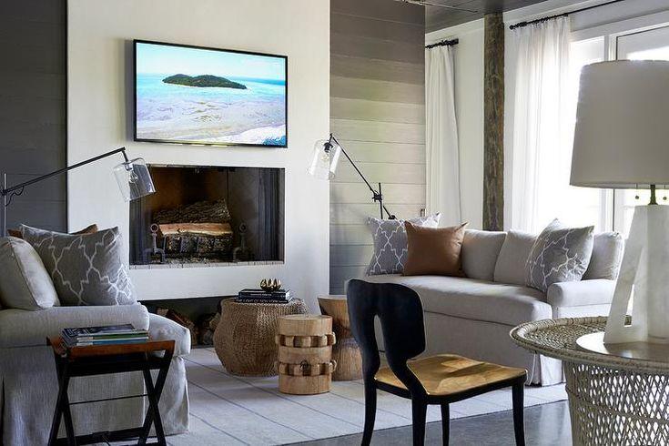 Modern cottage living room features black shiplap walls ...