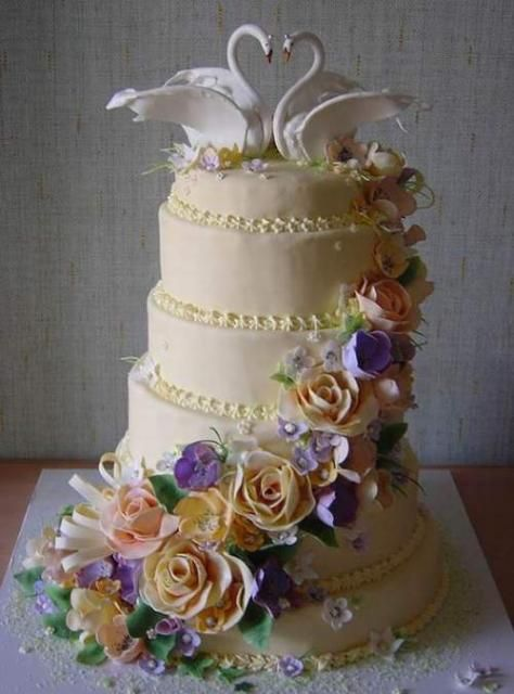 Beautiful Ivory cake with peach, purple and pink flowers. Swan topper.