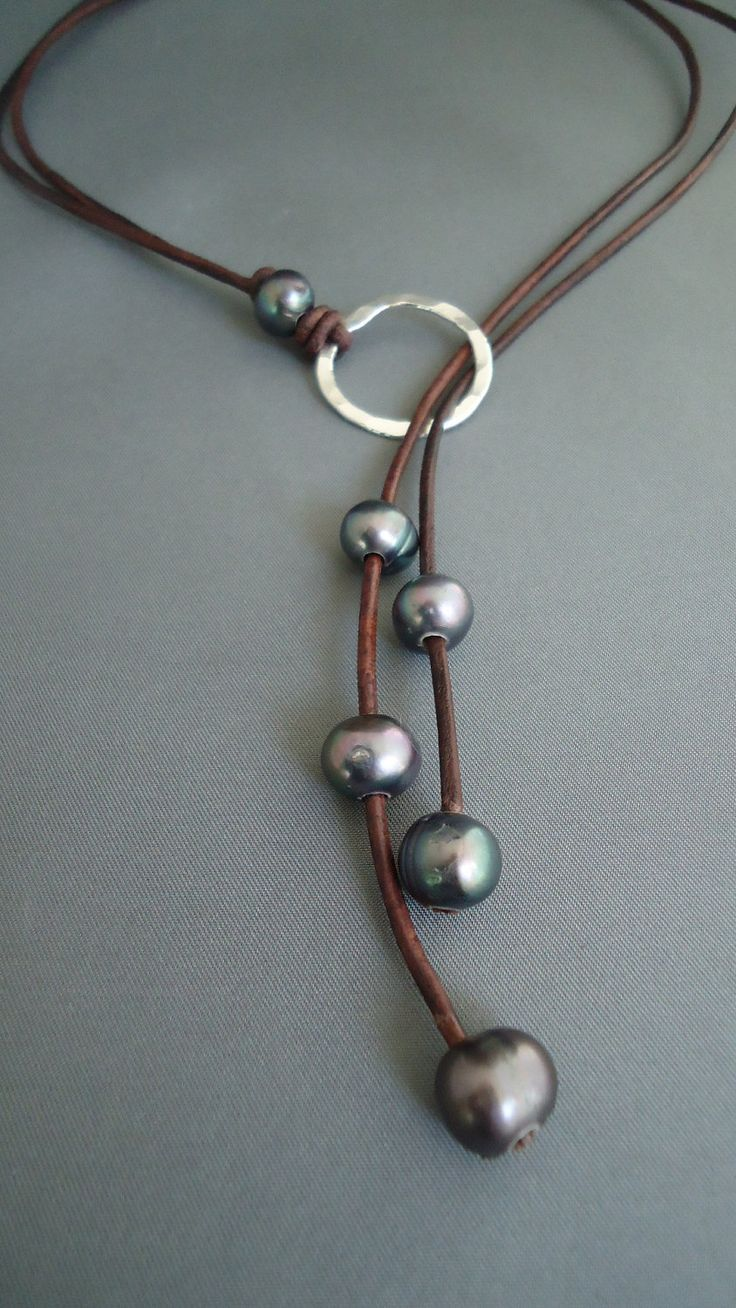 This lariat is made with 5 lustrous 10-11 mm cultured pearls strung on high quality vintage brown leather and knotted with a single pearl on to a 29 mm forged and soldered (by me) sterling silver ring. The total length is about 22 inches when on. Lariat c