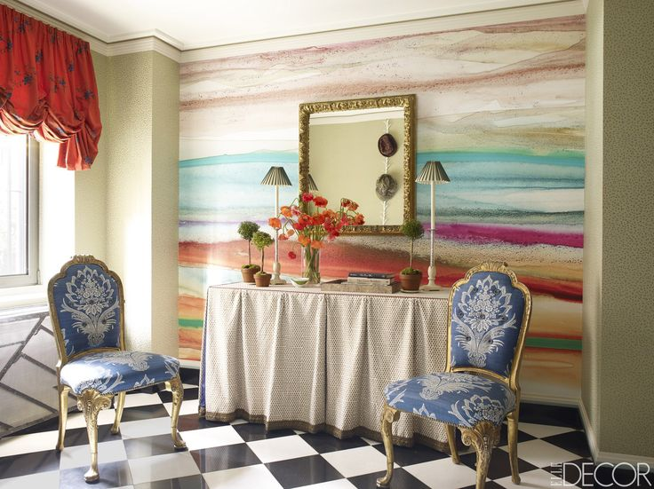 A pair of 19th-century Queen Anne–style chairs and a circa-1820 French mirror in the entry. The table is covered with a Raoul Textiles linen, and the wallpaper is by Peter Fasano, with a central panel featuring a digital image.   - ELLEDecor.com