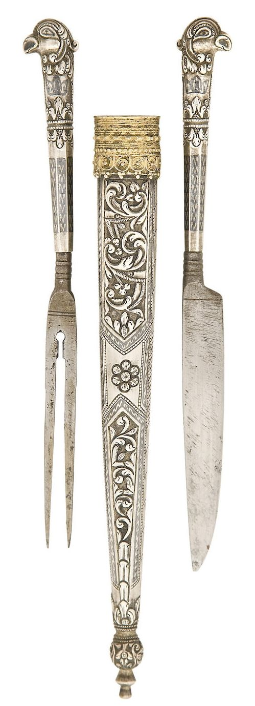 Ottoman / Armenian nielloed silver travelling cutlery set (trousse), late 18th century, knife with single edged blade, fork with two sharp tines, silver handles cast and chased with a medial band of foliage and with a bird's head pommel in the round, the tapering lower half with nielloed decoration, silver scabbard embossed and chased with panels of foliage within nielloed borders, bud-shaped finial chased with foliage, gilt filigree locket, and small ring for suspension 9.7 cm. blade.