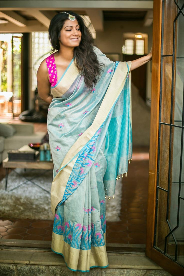 Cool light blue in a durable jute tussar drape, for all your summer soiree needs! With delicately worked cross stitch flowers in pink and blue and a subtle gold tissue border. This saree spells femininity all the way.Pair with a pink blouse, a blue blouse or even a gold blouse for those special occasions. #tussar #blue #saree #India #blouse #houseofblouse