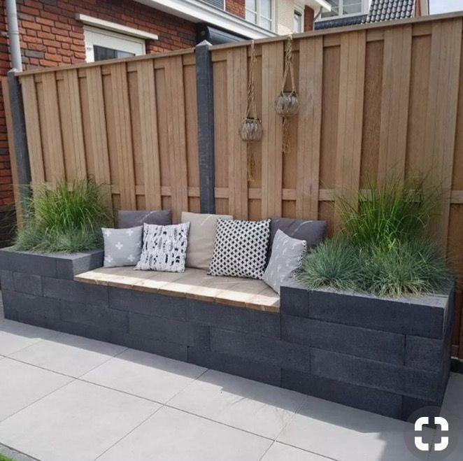 Einfach eingebaute Bank und Pflanzgefäß mit einem schönen Zaun dahinter