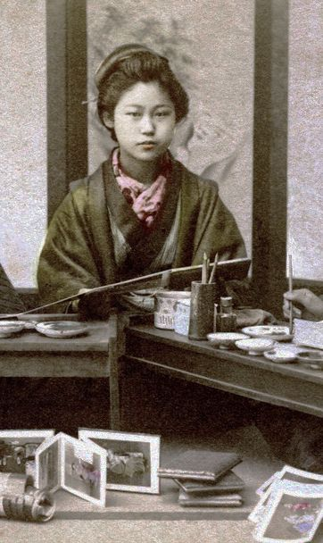 [detail] of young Japanese woman pausing from her work hand-coloring b&w photographs. Yokohama, Japan, about 1910. Image via Okinawa Soba on Flickr