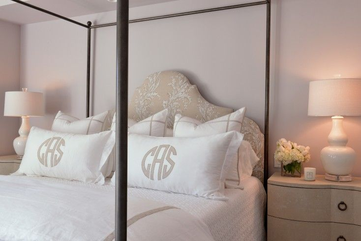 White and beige bedroom boasts an iron canopy bed with beige arched headboard on queen bed dressed in white and beige hotel bedding and white and beige monogram shams flanked by 3 drawer curved nightstand topped with white gourd lamps on lucite bases.