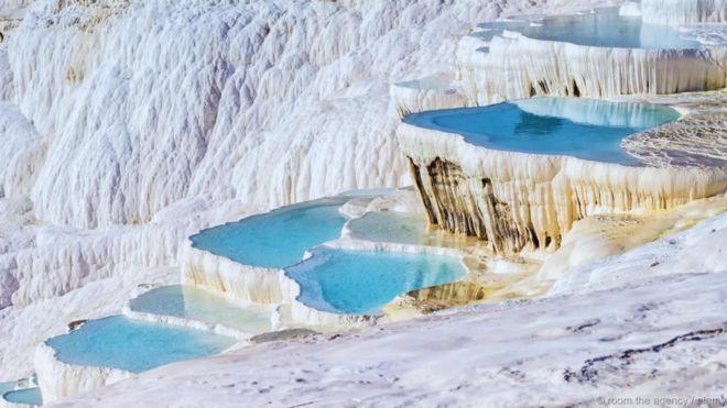 Hồ bậc thang Pamukkale Travertine, Thổ Nhĩ Kỳ. Những hồ nước màu ngọc lam nằm như bậc thang trên triền đá vôi này là nơi từng có những dòng suối nước nóng giàu khoáng chất chảy qua. Còn được gọi là Lâu đài Bông, khu địa hình bậc thang Pamukkale nằm cạnh thành phố La Mã cổ Hieropolis. Toàn khu địa hình này cùng thành phố cổ được gộp chung được UNESCO công nhận là Di sản Thế giới.