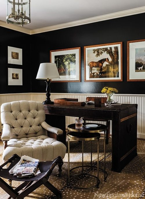 Black walls in traditional office with leather wrapped desk, with cream beadboard wainscoting and antelope print carpet.