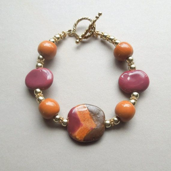 These fun Kazuri beads look like candy especially when they include butterscotch - so bright and colorful and scrumptious! The bracelet is 7.5 inches finished with a gold-plated pewter toggle clasp. The hand-painted Kazuri focal bead is surrounded by butterscotch round and burgundy bean-shaped Kazuri beads. The bracelet is accented with 14K gold-filled beads. Free Shipping within the U.S.! The piece will be contained in a small lilac organza drawstring pouch with a description of the…