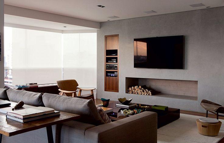 O duto desta lareira foi aproveitado para criar na parede o volume de alvenaria e instalar a TV no alto. A fiação é levada por conduítes para o forro de gesso no teto, onde ficam as caixas de som. Projeto do escritório Messa Penna