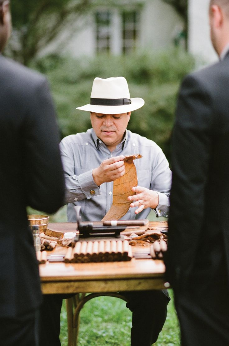 Cigar roller at a wedding reception. Cigars made by Cortez Cigars, image by Kristen Lynne Photography.
