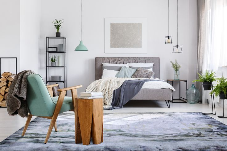 Handmade carpets bring warmth and enhance the style of the room. Cement design for the Scandinavian design bedroom.