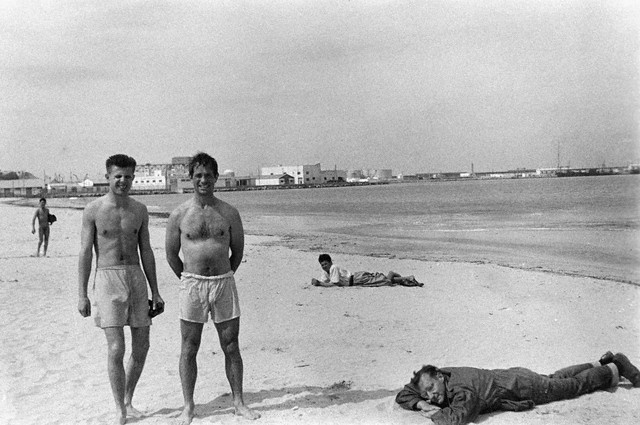 Peter Orlovsky, Jack Kerouac and William Burroughs Relaxing on Beach  Poets Peter Orlovsky and Jack Kerouac pose in swim trunks, converted boxer shorts, as William S. Burroughs takes a nap fully clothed on a beach in Tangier, Morocco.