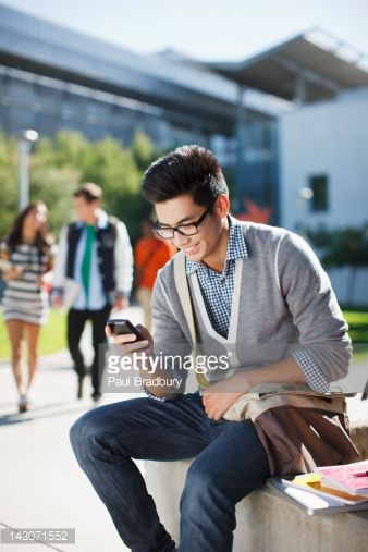 Stock Photo : Smiling student using cell phone outdoors
