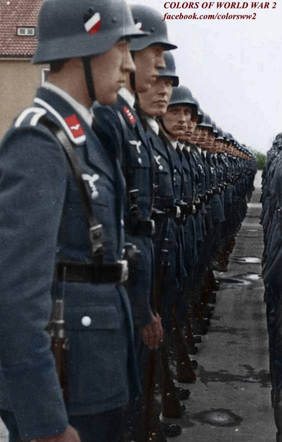 Cleanly-dressed German Luftwaffe soldiers stand neatly and orderly in formation during a routine inspection from commanding officers. The officers will ensure the troops are clean-cut, in fighting physical shape, dressed accordingly, inspect the condition of their firearms, check on squad morale, ensure supplies are adequate, and ensure discipline and obedience is invoked within every soldier.
