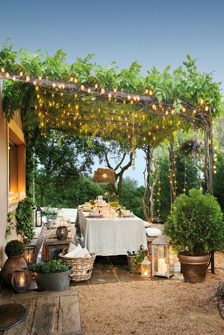 outdoor dining area under a vine-covered pergola with wooden table and benches and lots of fairy string lights. Backyard terrace porch inspiration. Ho…