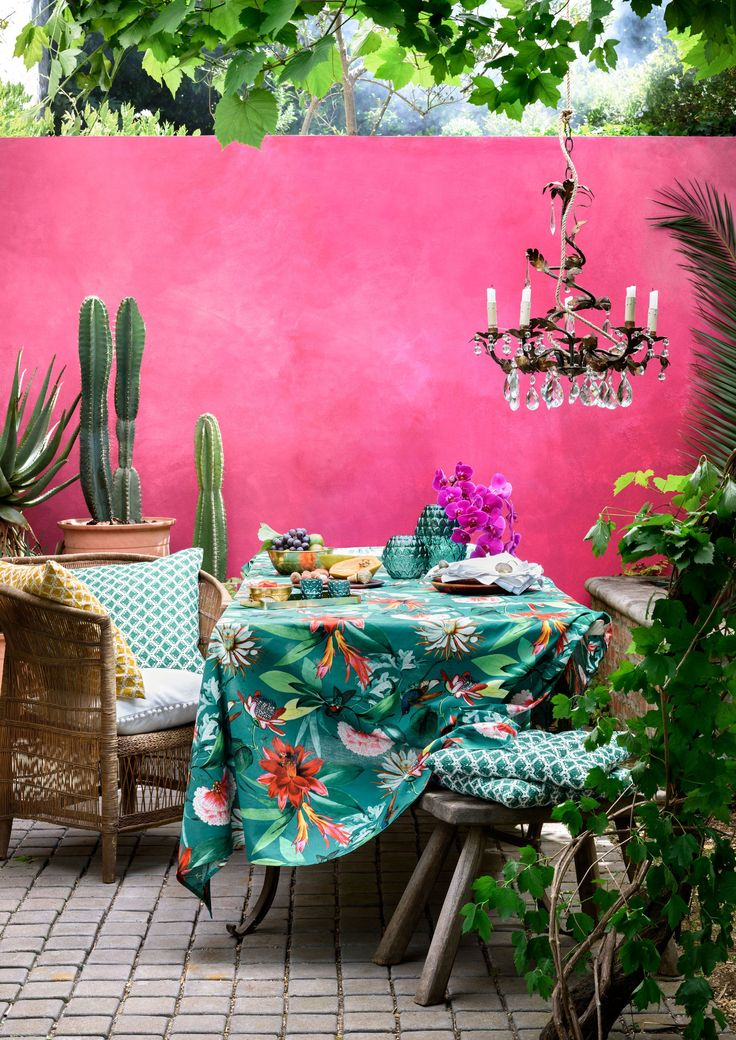 Colorful Morrocan style patio. Pink walls, botanical print table cloth, chandelier and indoor plants.
