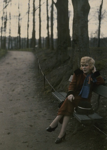 Maynard Owens Williams. 1920s. French woman sitting on a park bench in early evening, Tete d'Or Park, Lyons, Rhone, France.