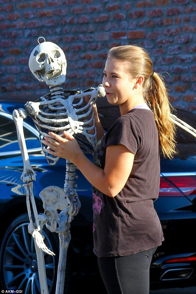 Spook-show: The 17-year-old conservationistheld the plastic bony frame in a closed pose, as she shot footage for the ABC show's Hallow'een special