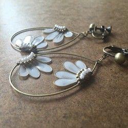 この作品を売るかどうか迷ったくらい、出し惜しんだ作品です。花が浮遊しているかのようなデザインは、水辺の花が浮かんでいるのを見てアイデアが生まれました。液体樹脂の透明感を活かすのには、このデザインだと思いました。澄んだ白色の花が、華やかに咲きました。こちらの作品は細いワイヤーに液体樹脂を漬けて、膜を形成して、花弁を作ったものになります。また、パールや金古美のビーズを使って高級感を出しました。金具変更について:①金属ピアス(チタン)②樹脂ポスト③金属フック④樹脂フック(白,透明、黒、ゴールド)を選んでください。備考に記載してください。 なおノンホールピアスには対応していません。大きさ:縦モチーフ4、3cm、重さ2g検索用: ピアス イヤリング 結婚式 浴衣 透明 白 ゴールド 結婚式 着物 お祭り 入学式 卒業式 パーティー ドレス 二次会 アメリカンフラワー ディップアート お正月 和服 和 2017新作 『特別企画1705』