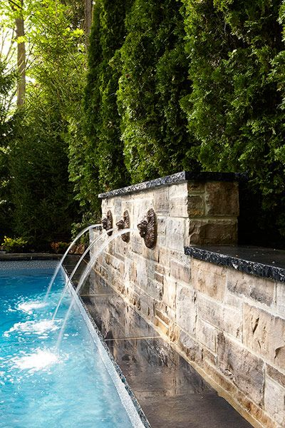 fountains into pool, stone wall, evergreens